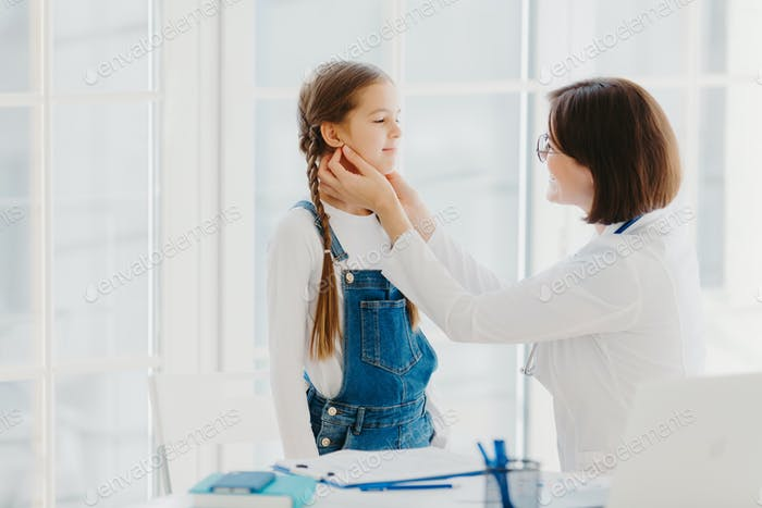 Female paediatrician examines child's throat, being professional skilled paediatrician