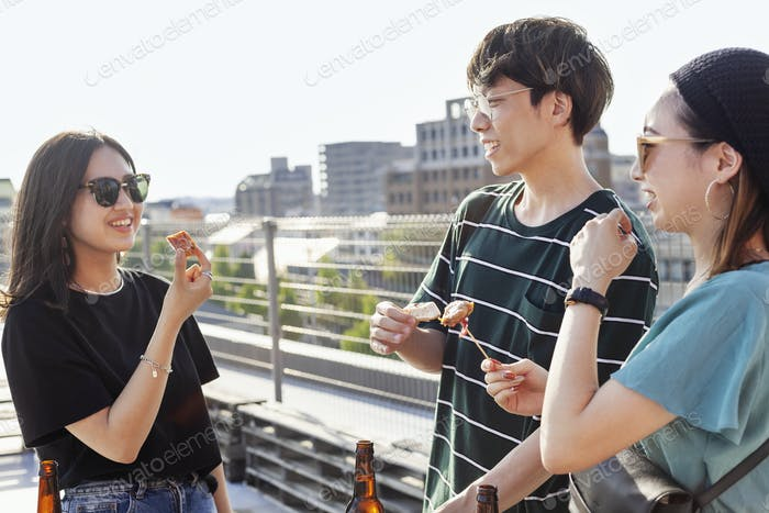 Young Japanese man and two women standing on a rooftop in an urban setting, drinking beer.