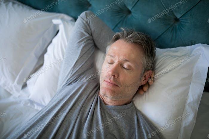 Man sleeping on bed in bedroom