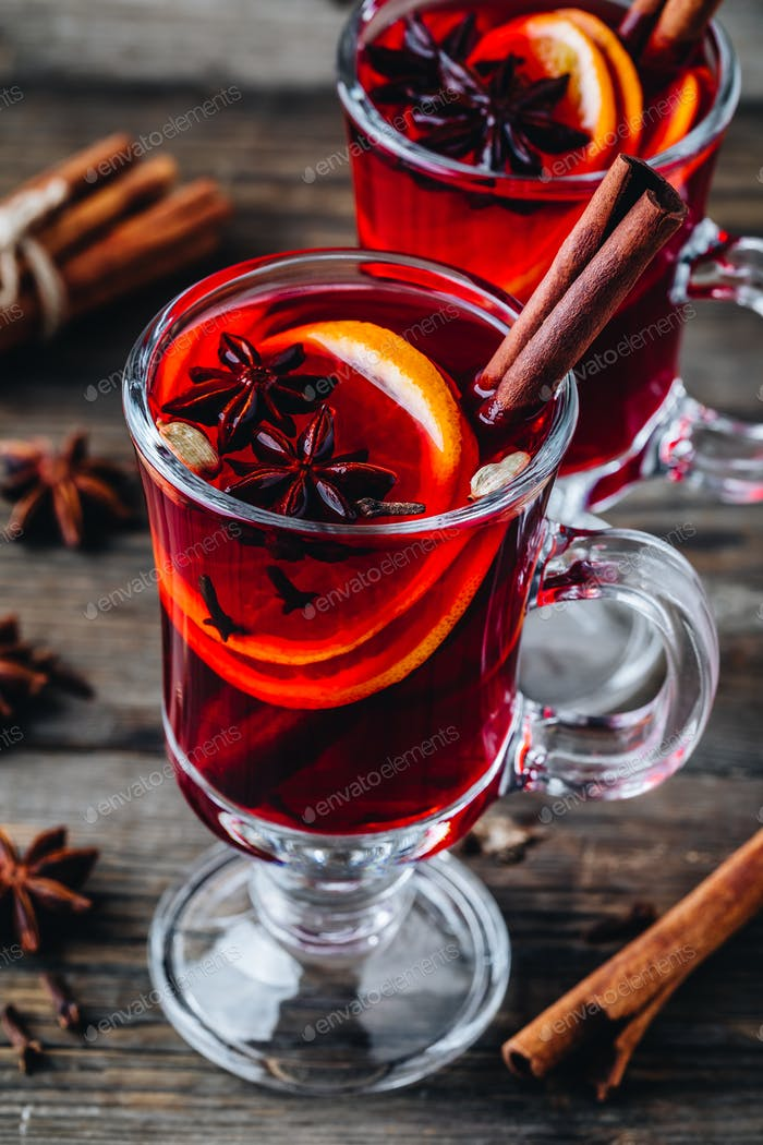 Mulled red wine with spices and orange in glass on a wooden rustic background.