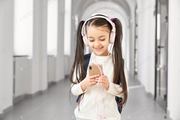 Schoolchild with headphones listening music