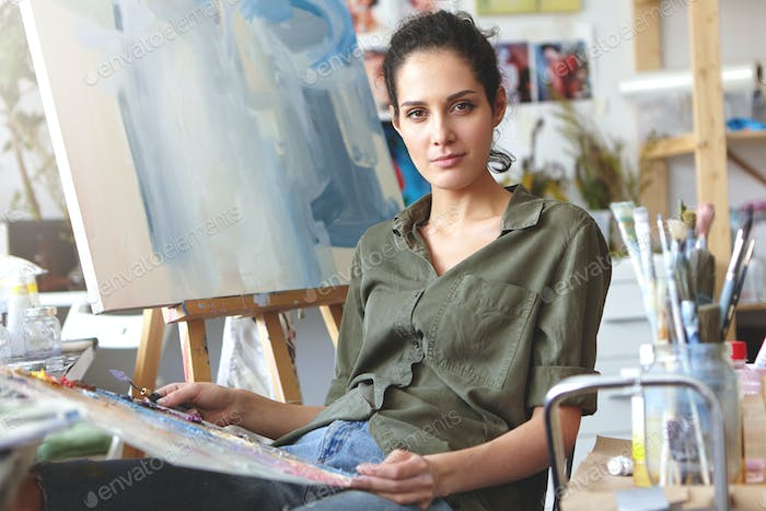 Picture of attractive professional young Caucasian female in casual clothes holding palette and pain