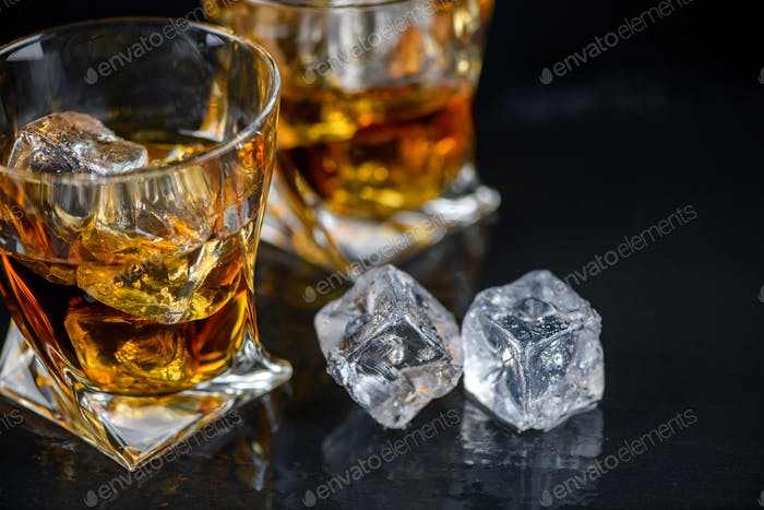 Glass of whiskey with cube ice on black background