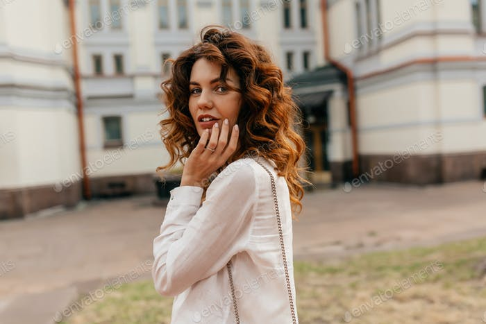 fascinating adorable lady with curls posing at camera on the street with lovable smile