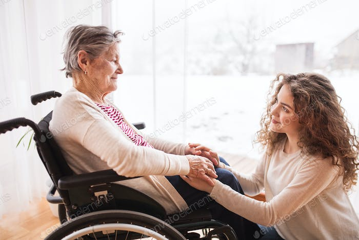 A teenage girl with grandmother at home, holding hands.