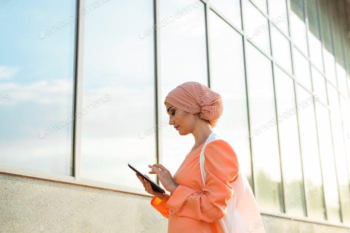 Porträt einer arabischen Geschäftsfrau in Hijab hält eine Tablette.