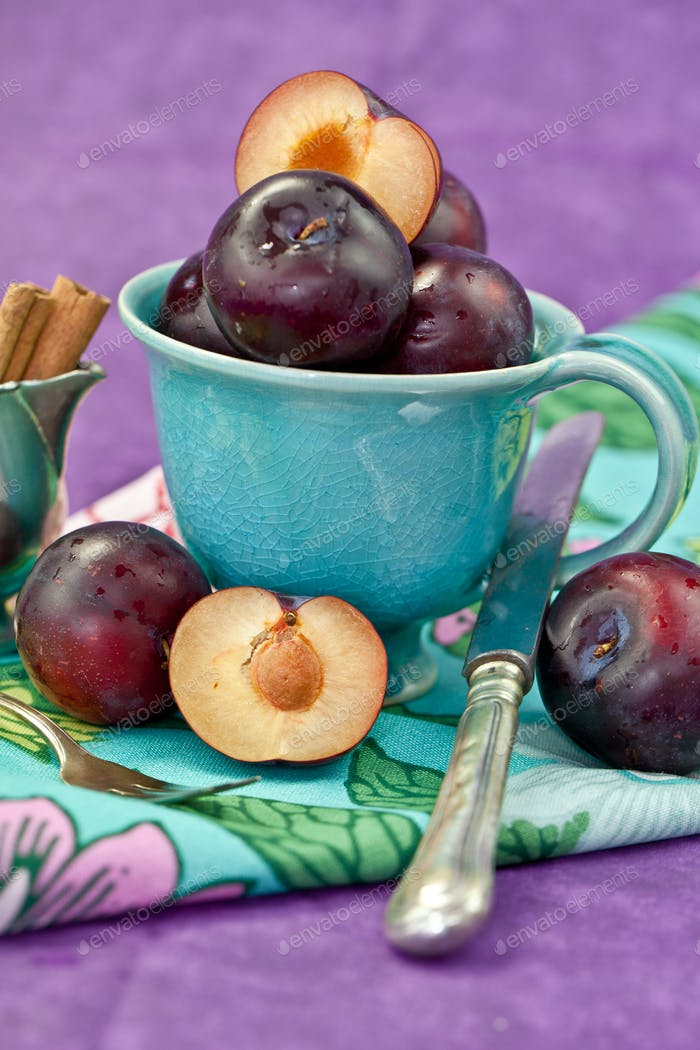 Fresh ripe plums in a vintage blue cup