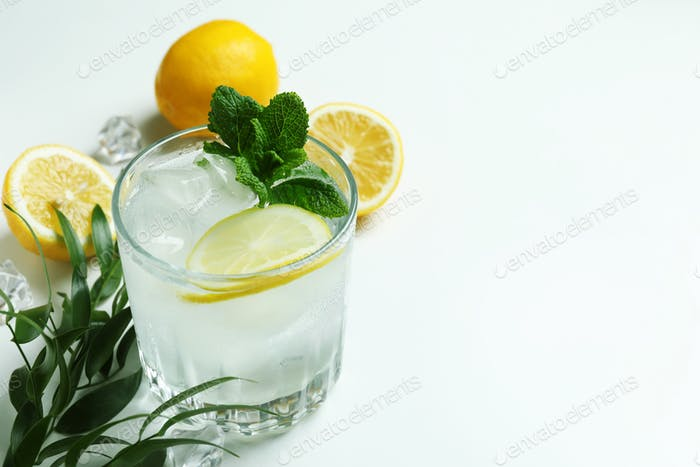 Glass of cocktail with lemon on white background