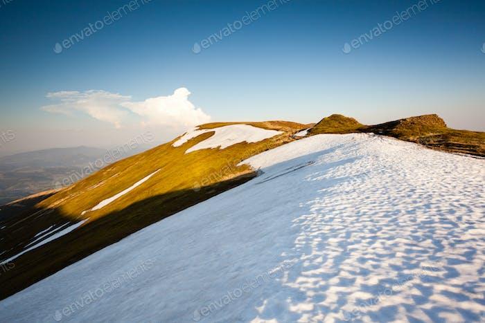 Berg mit Schnee und Gras, sonniges Wetter