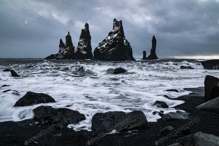Basalt rocks Troll toes on black beach. at storm Reynisdrangar, Vik, Iceland