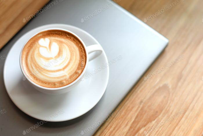 White latte coffee cup, decorated with leaves on the laptop placed on a wooden floor.