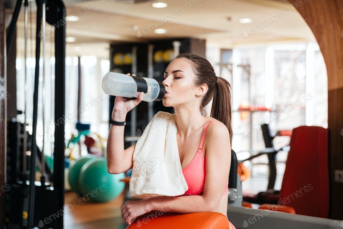 Woman athlete drinking water on training in gym