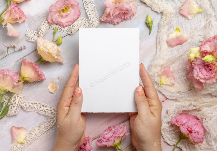 Hands holding a blank card over a marble table