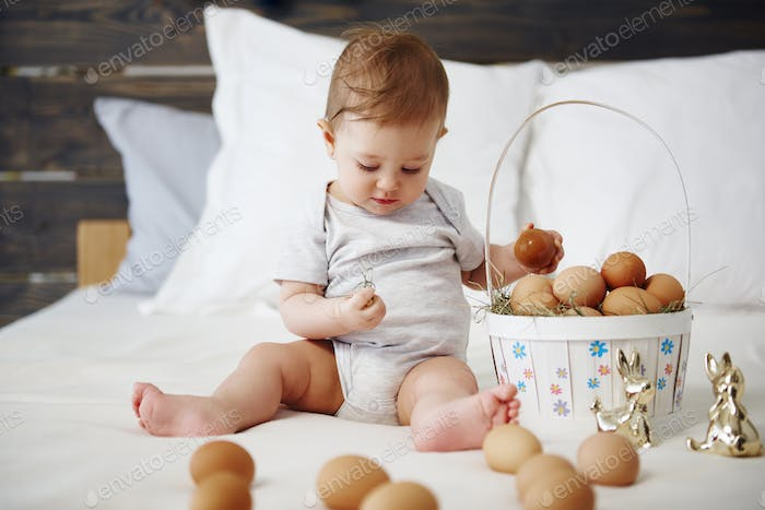 Baby with easter basket of eggs