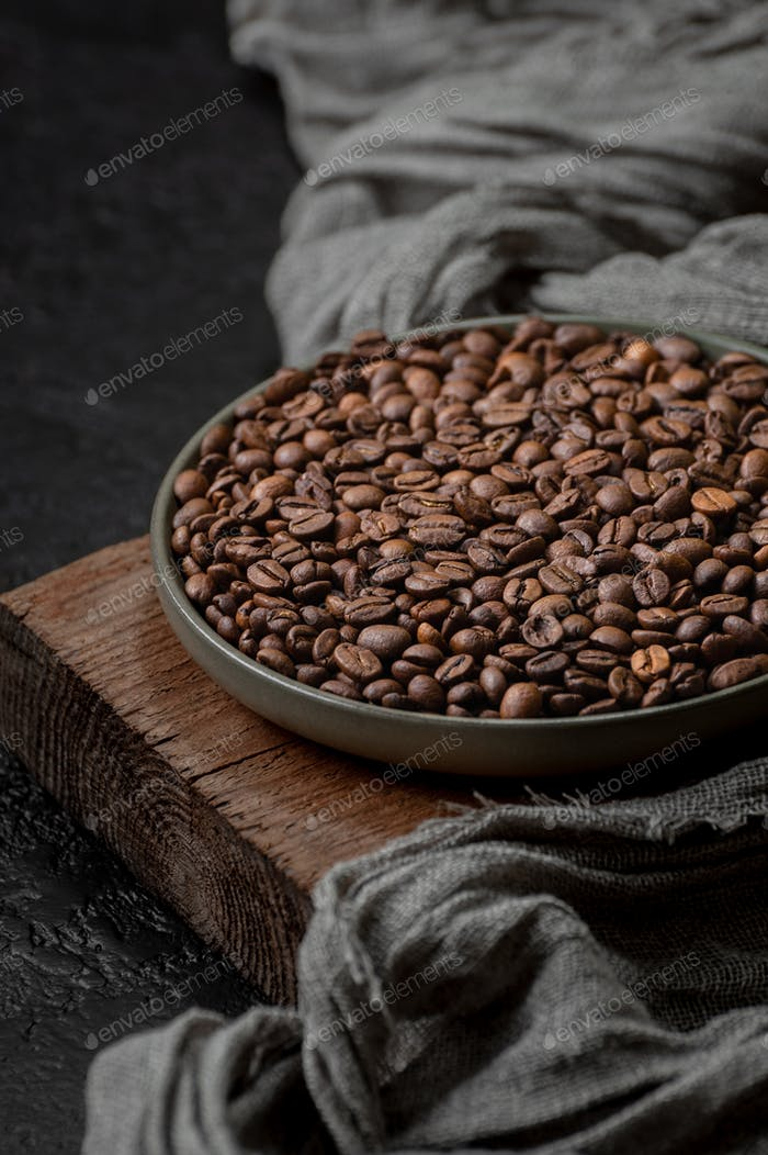 Roasted coffee beans in a plate on a wooden stand.