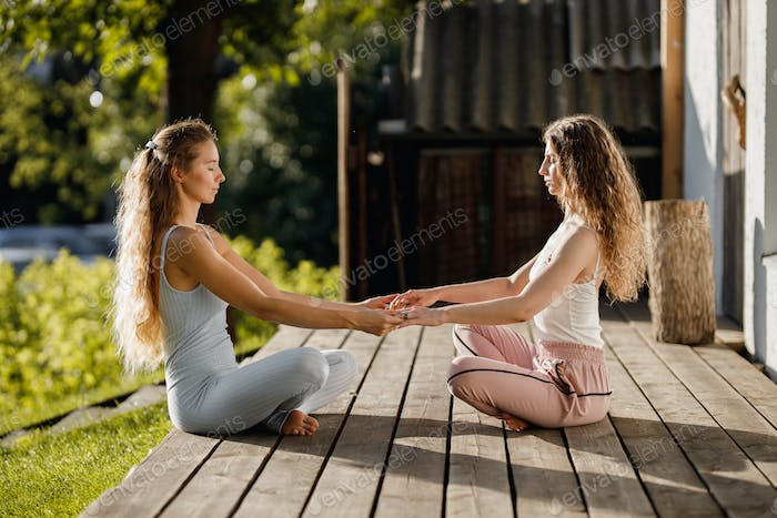 Two young women are sitting and holding hands in the lotus position on a wooden podium in the garden