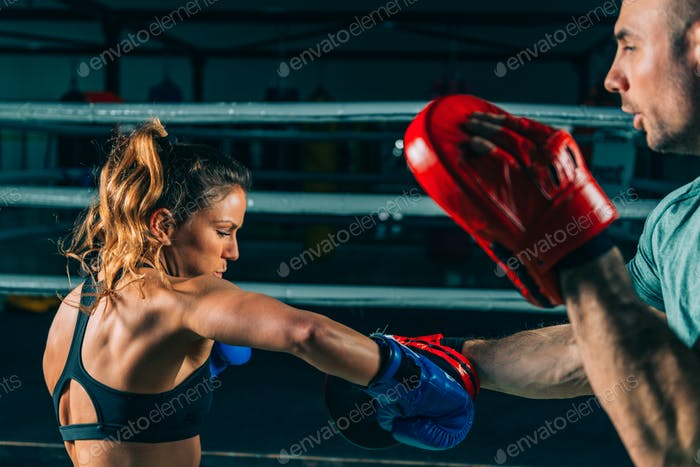 Woman on boxing training with trainer