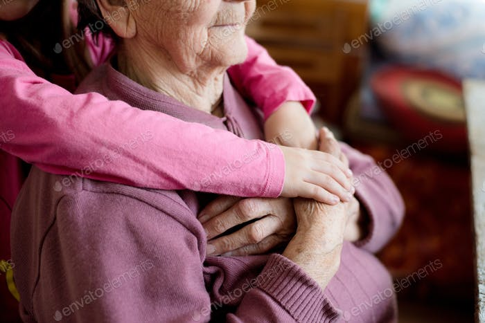 Unrecognizable granddaughter holding hands of her grandmother