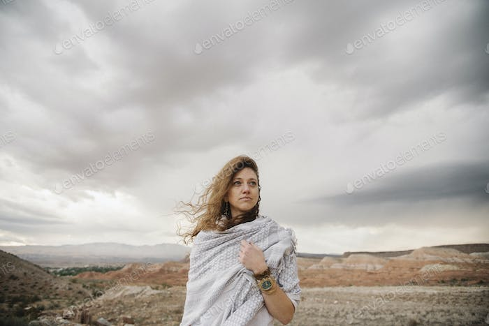 A woman with windblown hair wrapped in a shawl in a desert landscape