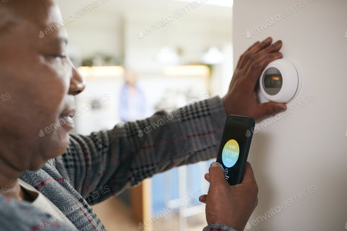 Mature Man Using App On Phone To Control Digital Central Heating Thermostat At Home
