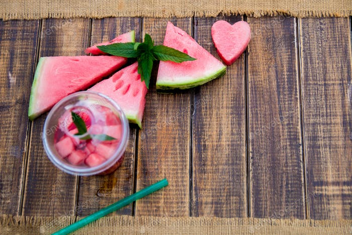 Watermelon cocktail with slice on wooden background. Heart carved from . Top view. Copy space.