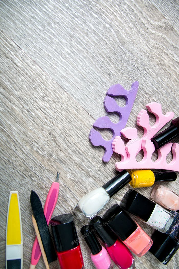 Set of nail polish and tools for manicure pedicure on a grey wooden background.