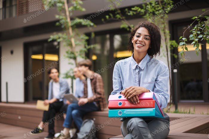 Pretty smiling lady sitting on bench with colorful folders on knees and happily looking in camera