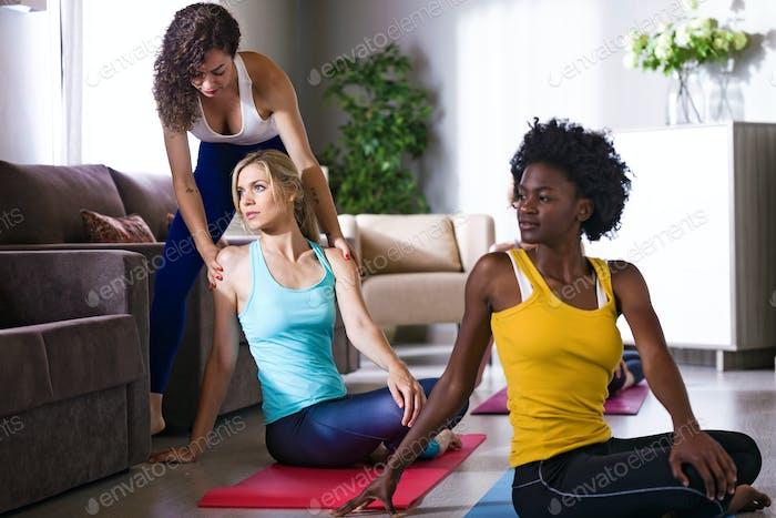 Hübsche Yoga-Instruktor hilft ihrem Schüler in einer Yoga-Sitzung bei