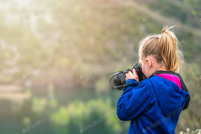 Little girl photographing nature