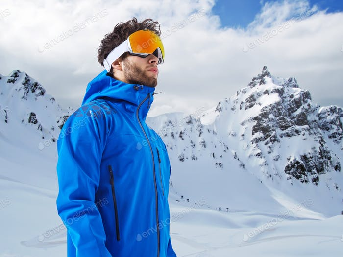 The mountaineer in winter clothes and ski ultraviolet protected mask against a snowy mountain