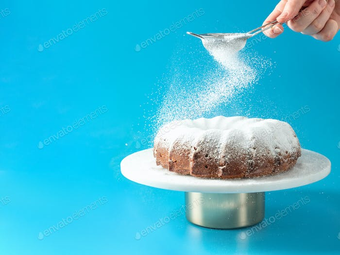 Female hand sprinkling icing sugar on bundt cake