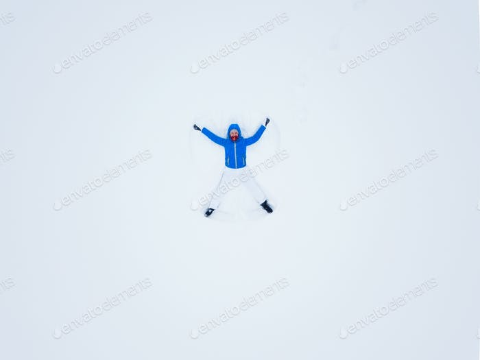 Aeriel view from the drone on woman making snow angels and playi