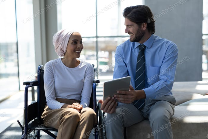 Disabled female executive with businessman discussing over digital tablet in the lobby at office