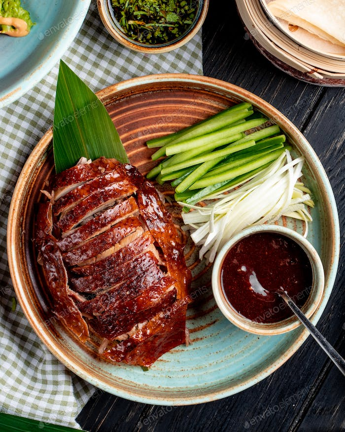 top view of traditional asian food peking duck with cucumbers and sauce on a plate