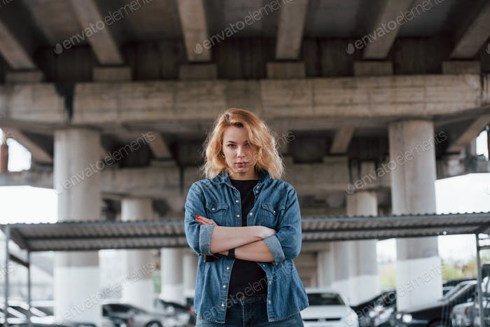 With arms crosses. Portrait of beautiful young woman standing under the bridge outdoors
