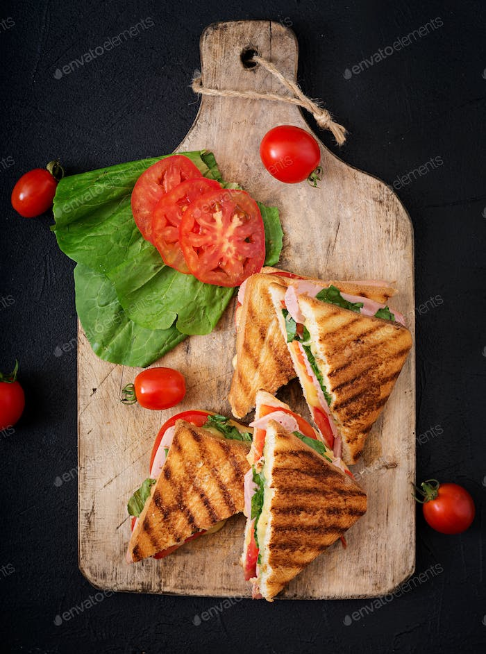 Club sandwich panini with ham, tomato, cheese and basil. Flat lay. Top view