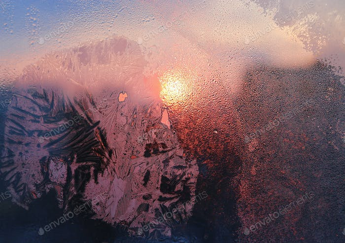 Ice patterns, water drops and sunlight on a window glass