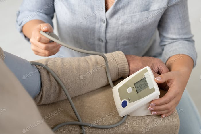 Hände der Frau mit Tonometer helfen älteren Vater, Blutdruck zu messen