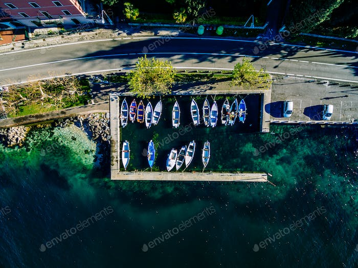 Aerial view of rural road by the sea with fishing boats in Italy