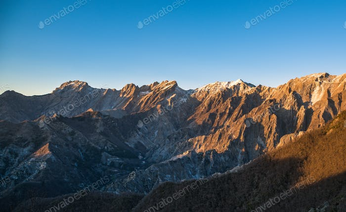 Apuane alpi snowy mountains and marble quarry at sunset in winte