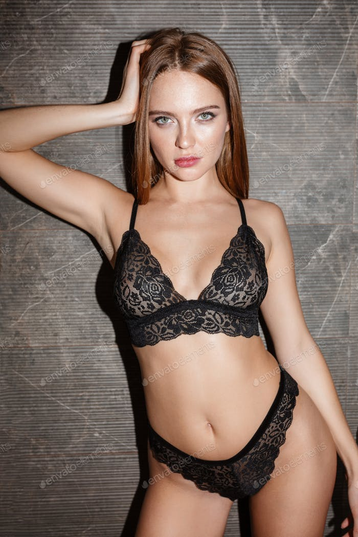 Young  beautiful woman standing in amazing black lingerie and dreamily looking in camera