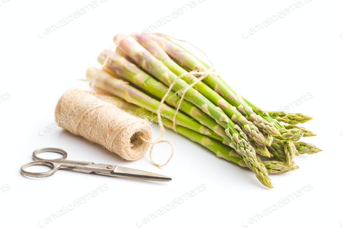 Fresh green asparagus with scissors and thread.