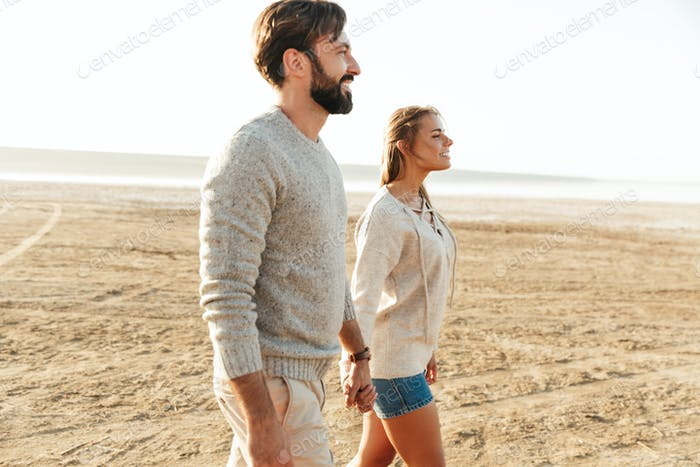 Loving couple outdoors at beach walking.