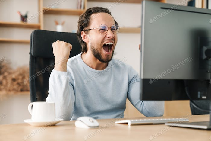 Image of programmer man making winner gesture working with computer