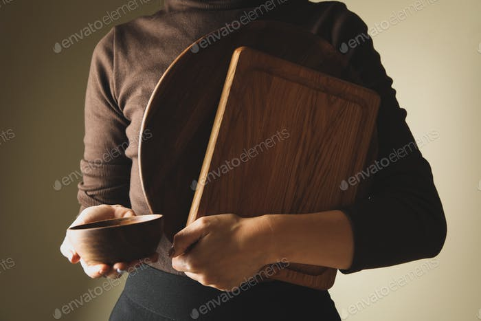 Young woman in sweater holding wooden kitchenware