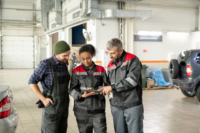 Three young workers of car maintenance center discussing technical information
