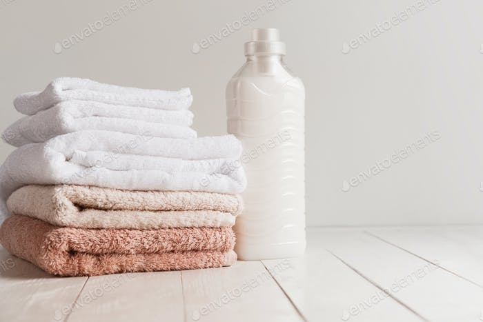 Bottle with gel for washing and a stack of fresh towels on a wooden table