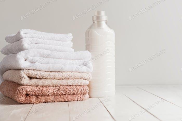 Flasche mit Gel zum Waschen und ein Stapel frischer Handtücher auf einem Holztisch
