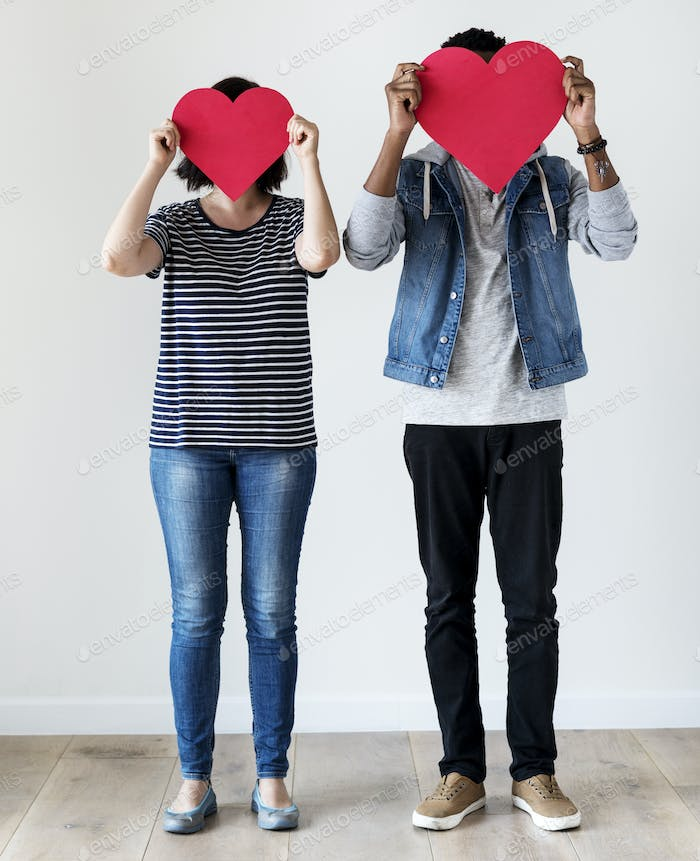 Happy interracial couple holding red hearts love and relationship concept