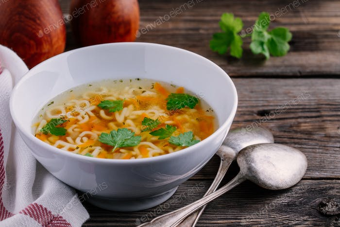 Homemade Chicken and Alphabet Soup with carrots and parsley in bowl